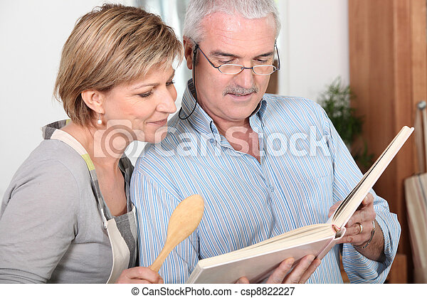 Mature couple looking at a recipe book - csp8822227