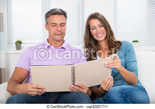 Mature Couple Looking At Photo Album - csp32201711