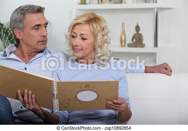 Mature couple looking at photo album - csp10892854
