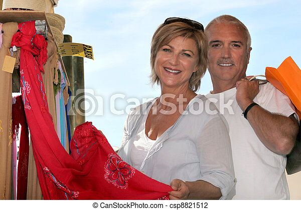 Mature couple looking at sarongs in a holiday shop - csp8821512