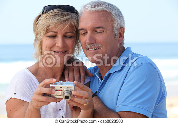 Mature couple looking at the photos on their digital camera - csp8823500