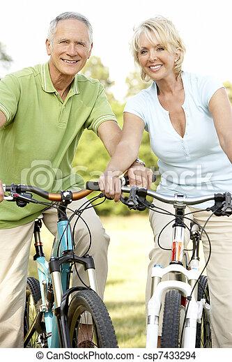 Mature couple riding bikes - csp7433294