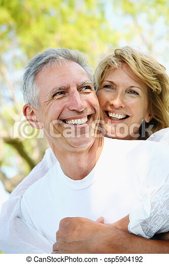 Mature couple smiling and embracing - csp5904192