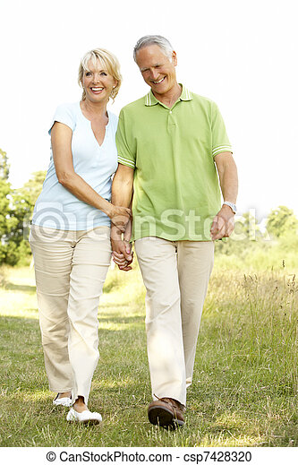 Mature couple walking in countryside - csp7428320