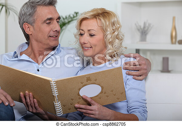 Mature couple watching a photo-album - csp8862705