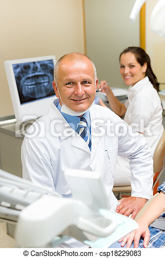 Mature dental surgeon in office with assistant - csp18229083