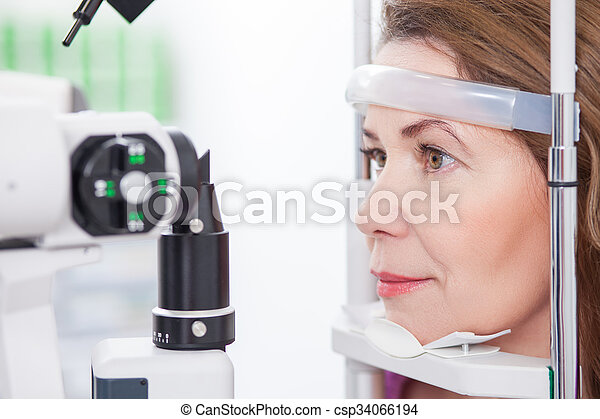Mature lady is looking into eye test machine - csp34066194