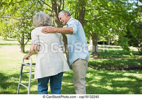 Mature man assisting woman with walker at park - csp18132240