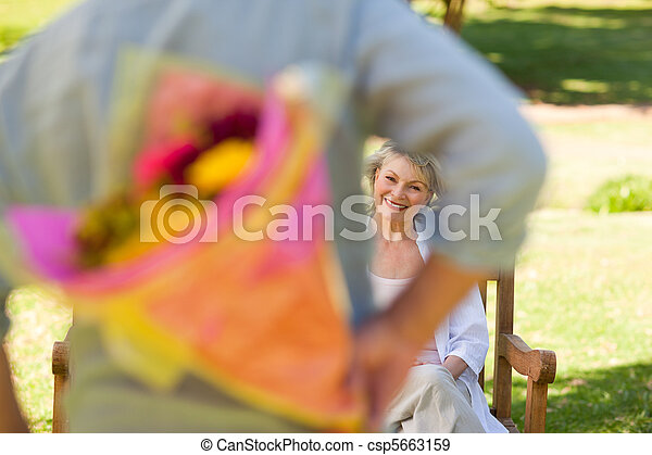 Mature man offering flowers to his wife - csp5663159