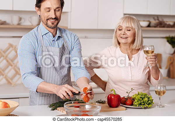 Mature son cooking dinner for his parent in the kitchen - csp45570285