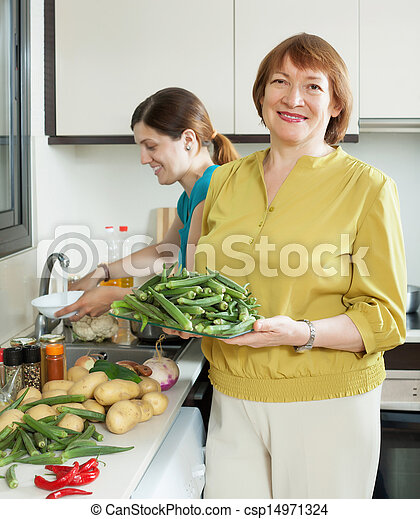 mature woman and adult daughter cooking vegetables   - csp14971324