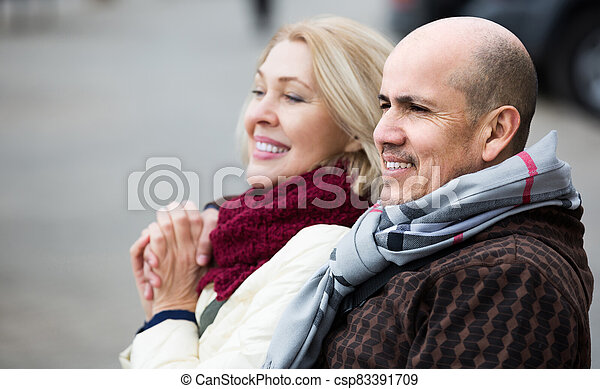 mature woman and elderly man posing together outdoors - csp83391709