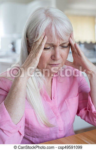 Mature Woman At Home Suffering From Headache - csp49591099