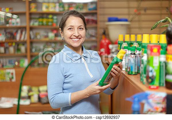 mature  woman chooses fertilizers at store   - csp12692937