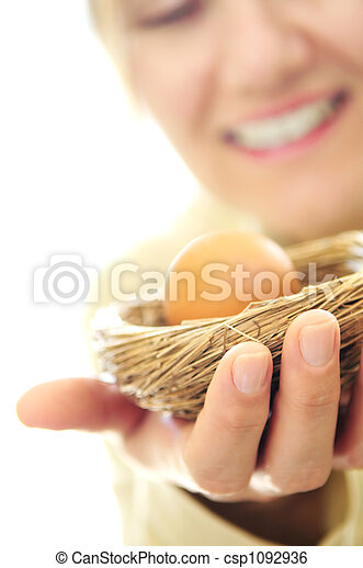 Mature woman holding a nest with an egg - csp1092936