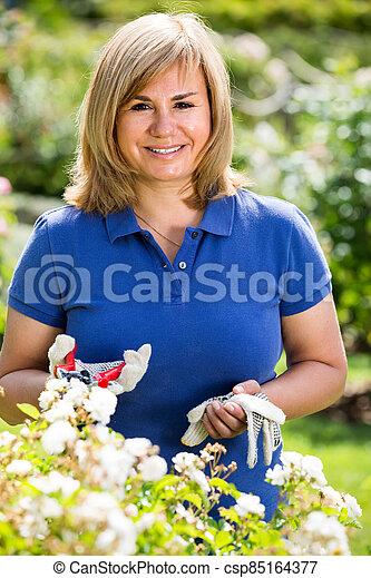 mature woman in garden on summer day. - csp85164377