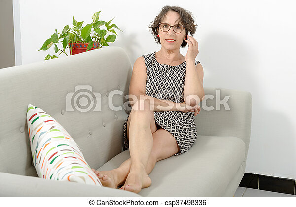 Mature Woman On The Sofa With A Phone Csp37498336