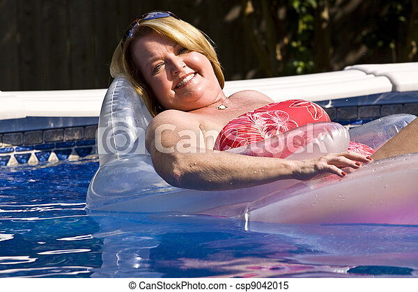 Mature woman relaxing at the pool. - csp9042015