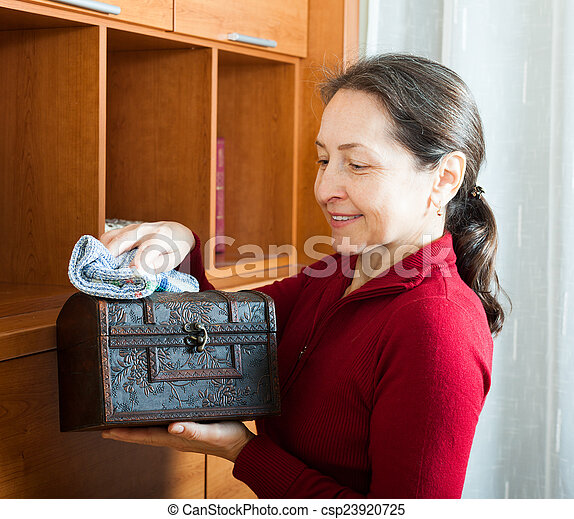 mature woman wiping dust from wooden chest - csp23920725