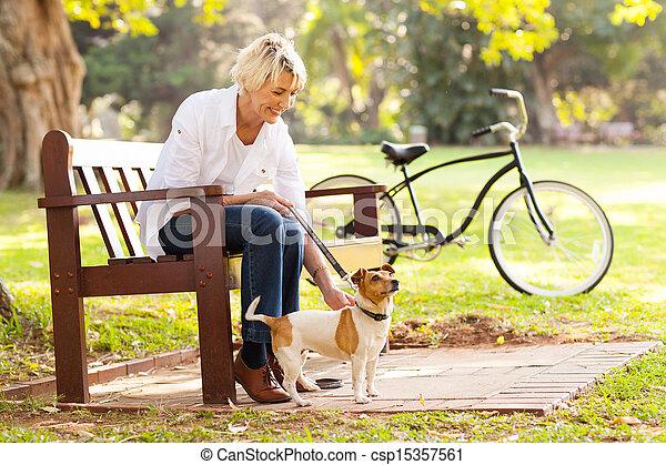 mature woman with pet dog outdoors - csp15357561