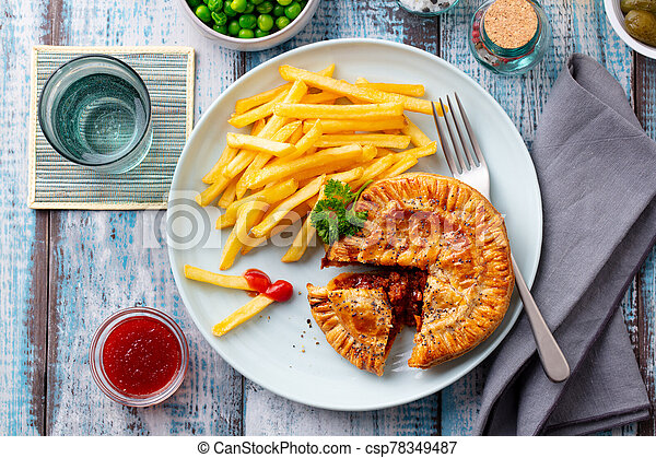Meat pie with french fries on a plate. Wooden background. Top view. - csp78349487
