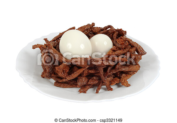 Meat sticks decorated in the form of bird nests with two boiled eggs. Isolated on white - csp3321149
