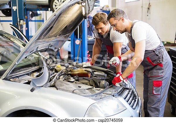 Dos mecánicos arreglando coches en un taller - csp20745059