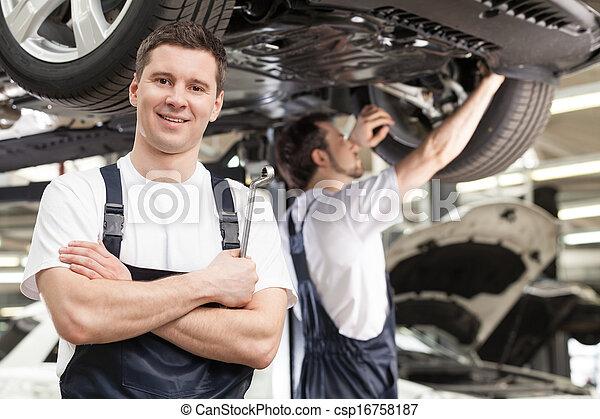 mecánica, posición, mecánico, el suyo, plano de fondo, trabajando, shop., trabajo, brazos, joven, confiado, mientras, cámara, cruzado, otro, sonriente, uno - csp16758187