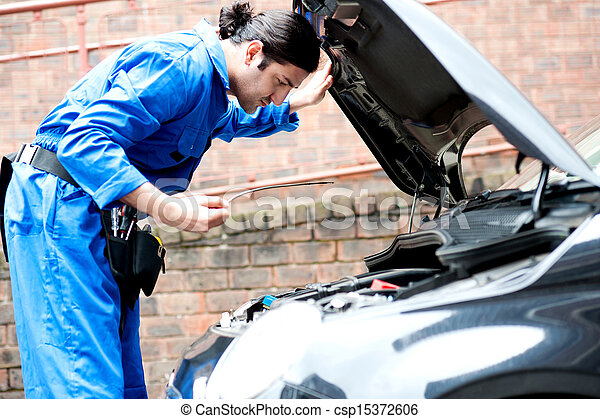 Mechanic checking the motor oil of the car - csp15372606