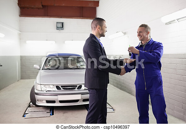 Mechanic giving car key while shaking hand to a client - csp10496397