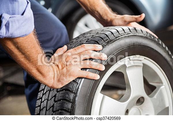 Mechanic Holding Car Tire At Garage - csp37420569