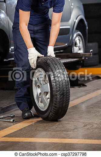 Mechanic Holding Car Tire At Garage - csp37297798