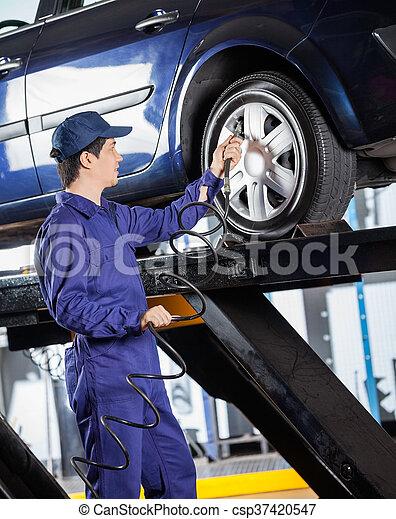 Mechanic Inflating Car Tire At Garage - csp37420547
