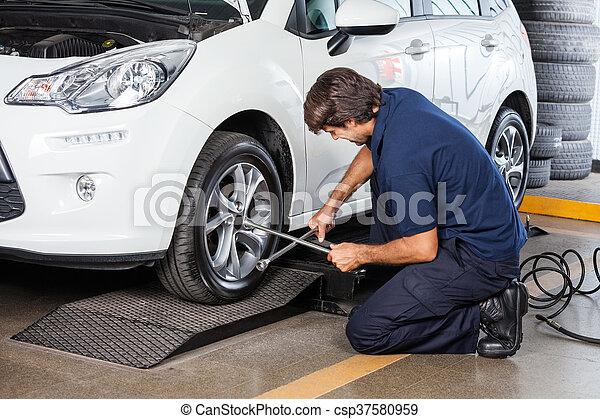 Mechanic Repairing Car Tire At Garage - csp37580959