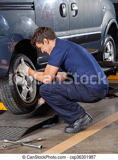 Mechanic Replacing Car Tire At Garage - csp36301987