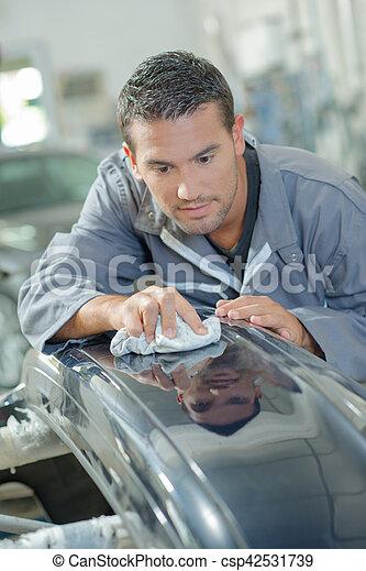 Mechanic rubbing metal with rag - csp42531739