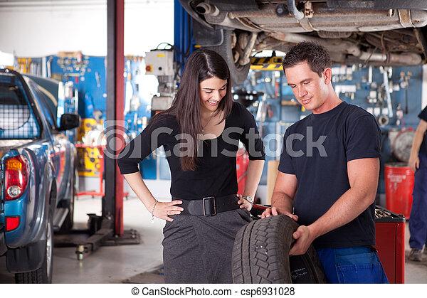 Mechanic Showing Tire to Woman Customer - csp6931028