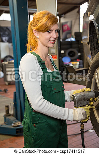 Mechanic with tools in garage replacing a tire on car - csp17411517