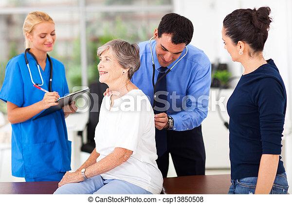 medical doctor examining senior patient - csp13850508