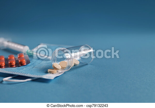 medical mask, syringe, tablets and vials with medicine on the blue background. Coronavirus, flu, disease concept. - csp79132243