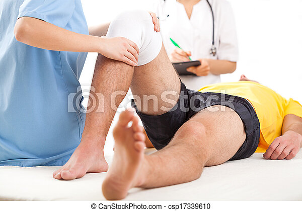 Medical team examining knee condition - csp17339610