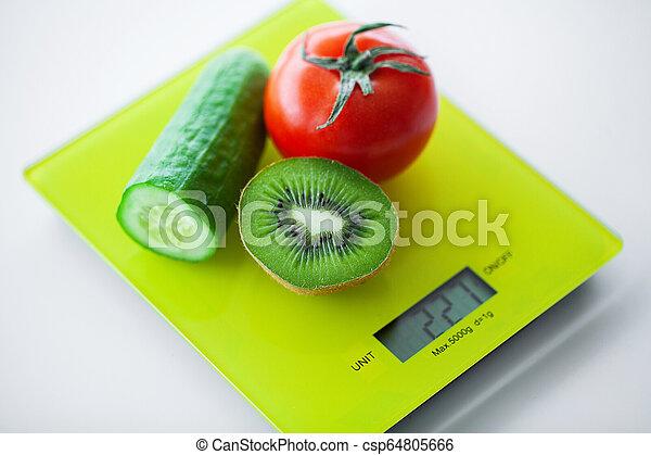 Dieta. Frutas y verduras con cinta métrica en la escala de peso - csp64805666