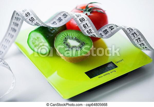 Dieta. Frutas y verduras con cinta métrica en la escala de peso - csp64805668