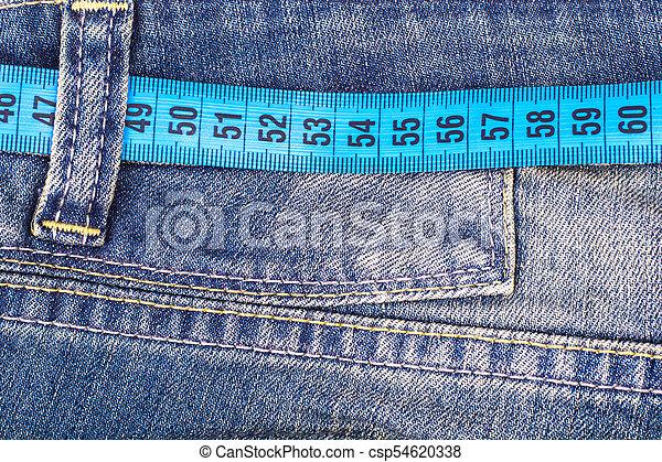Concepto el estilo de vida saludable, la pérdida de peso. Jeans con cinta métrica - csp54620338