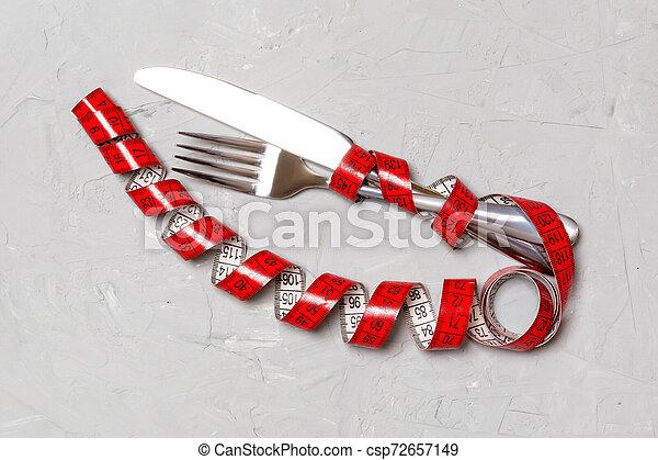 Concepto de dieta con tenedor, cuchillo y cinta métrica de fondo gris. La mejor vista de la pérdida de peso - csp72657149