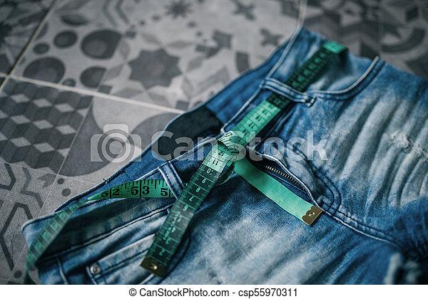 Midiendo cinta y jeans, concepto de pérdida de peso - csp55970311