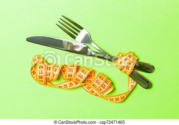 Concepto de dieta con tenedor, cuchillo y cinta métrica de fondo verde. La mejor vista de la pérdida de peso - csp72471463