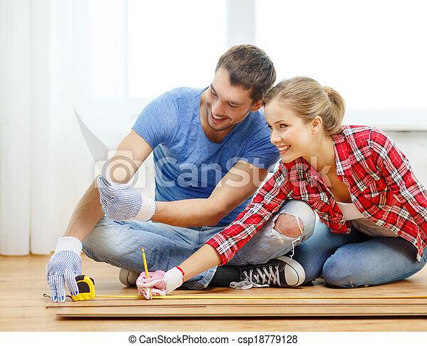 Pareja sonriente midiendo suelo de madera - csp18779128