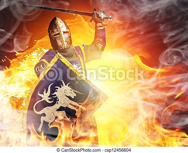 Medieval knight in attack position on fire background. - csp12456604