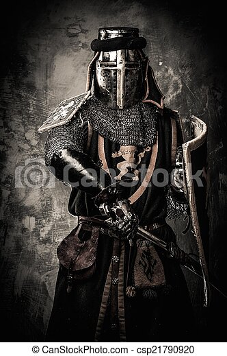 Medieval knight with a sword against stone wall - csp21790920